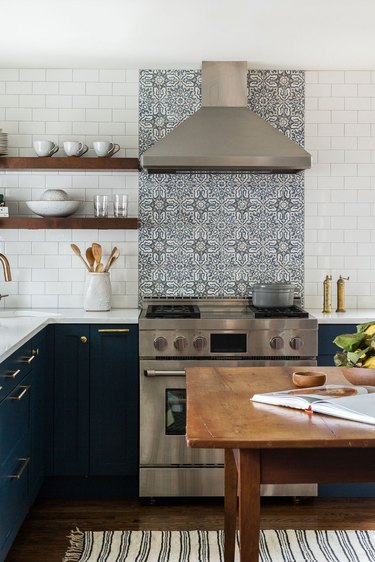 L-shaped kitchen with patterned stove backsplash and navy cabinets