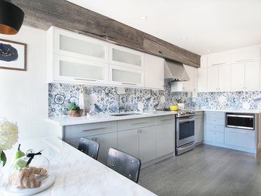 industrial L-shaped kitchen with white cabinets and patterned backsplash