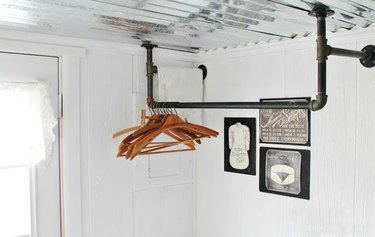Black cast-iron piping hangs from the ceiling of a white laundry room.