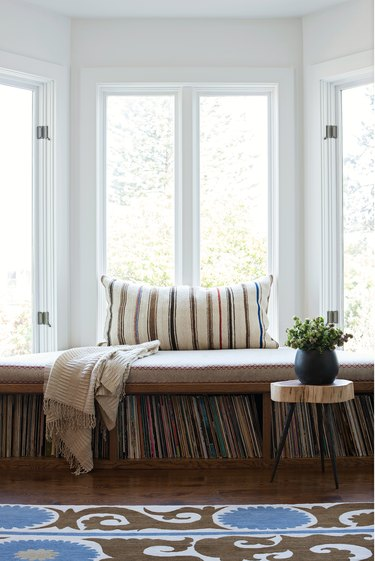 White bay window with pillow, a brown cushion, record player storage and wood side table with a plant.