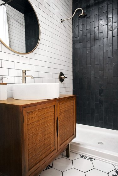 Photo of bathroom with black-and-white tiled walk-in shower.