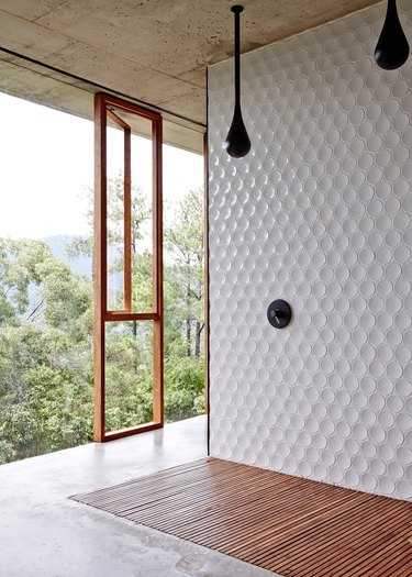 Round tiling in an open-air shower overlooking the trees.
