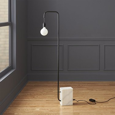 Minimal floor lamp with black L-shaped base and a single hanging round white bulb