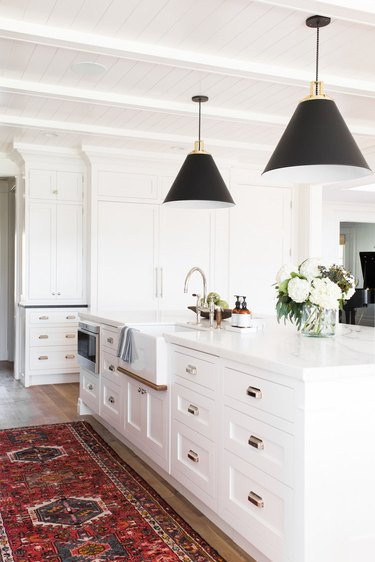 white kitchen with red runner in front of island with sink