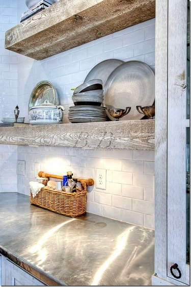 Zinc countertop and raw wood shelves with subway tile