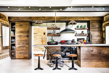 Rustic farmhouse kitchen with stainless steel appliances and wood wall paneling