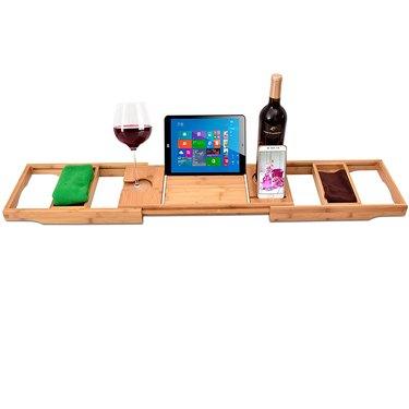 Blonde wood bathtub tray displaying tablet, wine and washcloths