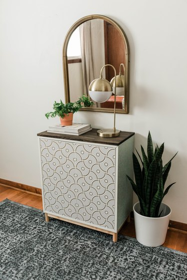 Entryway with mirror, credenza, plant, rug, brass globe table lamp.