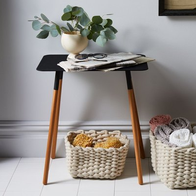 A simple, modern rectangular side table uniting form and function. Features a low maintenance, coated-steel tabletop on a base of slim wooden legs.
