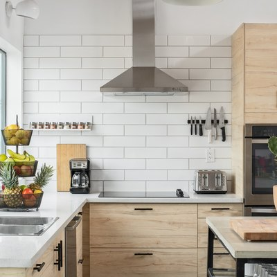 kitchen corner with white tiled walls, large windows, sink, pale wood cabinetry