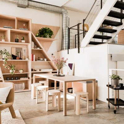 open living space with exposed staircase, bookshelves, dining table