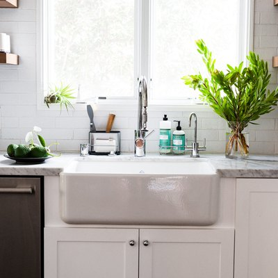 focus on farmhouse sink next to white countertop with large plant and sunny windows
