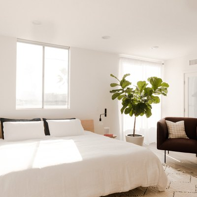 king size bed with white sheets in white bedroom