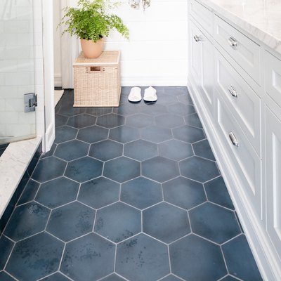 bathroom with hexagonal blue tiles, white cabinetry