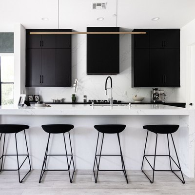 white kitchen with black cabinetry and chairs