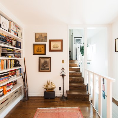 built-in bookcase filled with books and gallery wall near staircase