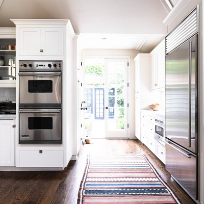 galley kitchen splitting a hallway leading outside, view of double ovens and striped rug
