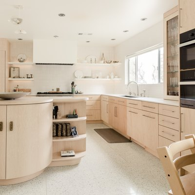 large kitchen with pale wood cabinets, round island, tile floor