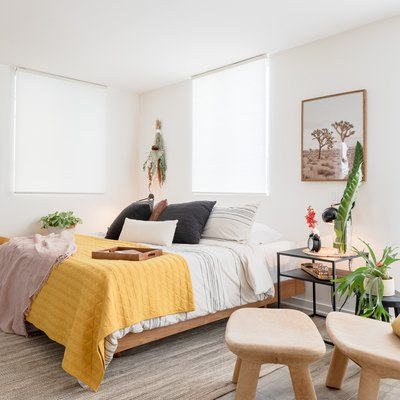 sunny bedroom with bed, windows, chair, yellow quilt