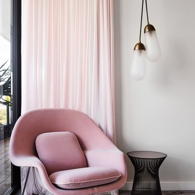 living room with pink lounge chair and drapery