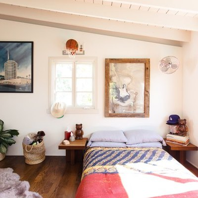 Bright colors in a beige bedroom with exposed beams and wood flooring