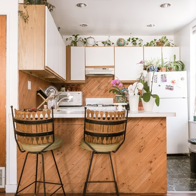 wood kitchen with white walls, white cabinetry, plants