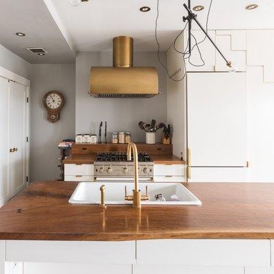 kitchen with bronze range hood, wood countertops and bronze plumbing fixtures