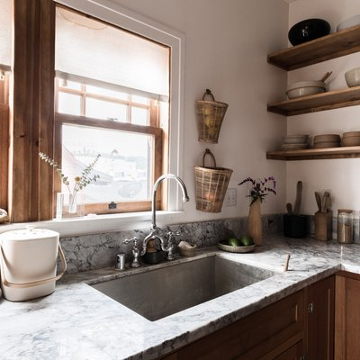 kitchen sink with double handles, grey countertops and wood kitchen cabinets