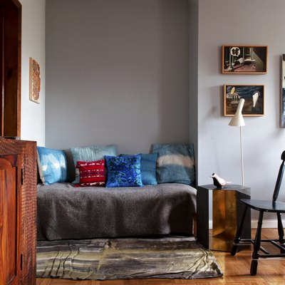 cozy nook with colorful pillows, art wall, and hardwood floors