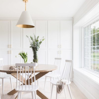 white dining room with ceiling pendant and built-in cabinetry