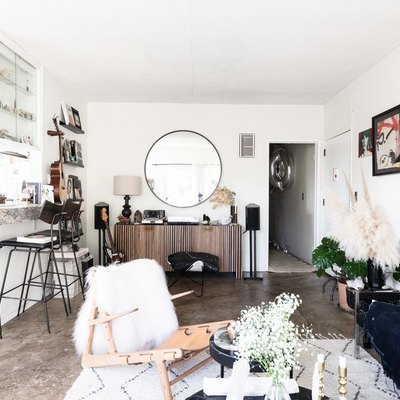 living room with concrete floors, bar stools and round mirror as focal point