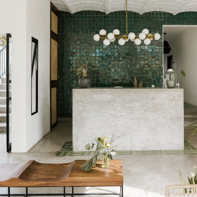 entry room with wooden table, concrete floor, scalloped ceilings, open to outdoors