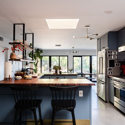 open kitchen with U-shaped peninsula, hanging shelves, blue cabinetry
