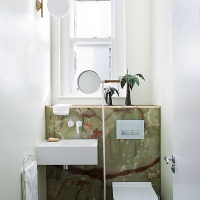 small bathroom with backlit panels of red-streaked green onyx