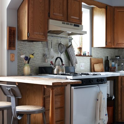 small kitchen with wood cabinetry and glass backsplash
