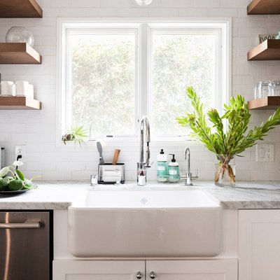 sunny kitchen with farmhouse sink and gray counters.