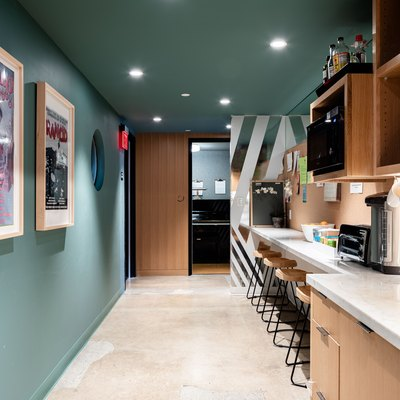 galley-style kitchen with green walls, overhead lighting and stools