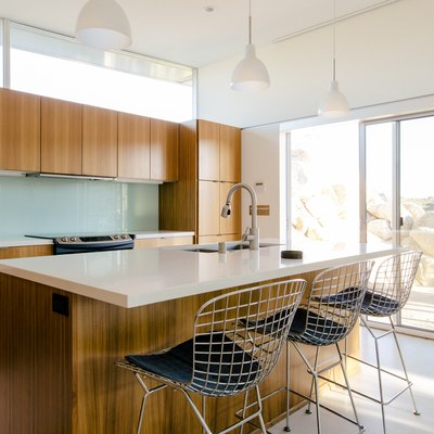 sunny kitchen with light countertop and wood cabinetry