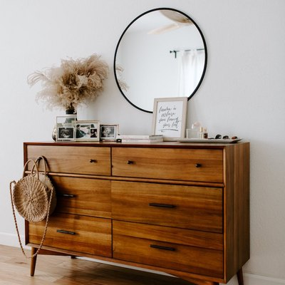 bedroom with wood dresser and round mirror