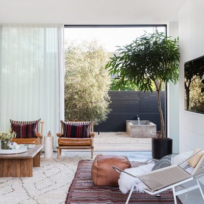 living room rug idea with big sliding glass doors in the background, in the foreground a wire chair and leather pouf sit atop a kilim rug layered over a flokati rug