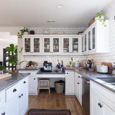 kitchen with white cabinetry, grey countertops and pull down kitchen sink faucet