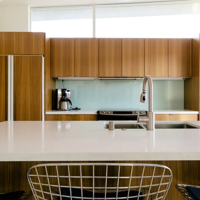 kitchen with natural wood cabinetry, kitchen island with white stone countertop and glass backsplash