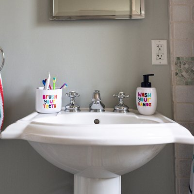 close up of bathroom pedestal sink with cup of toothbrushes and soap dispenser