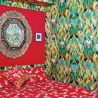 pattern filled bedroom with tropical wallpaper and ornate bedspread