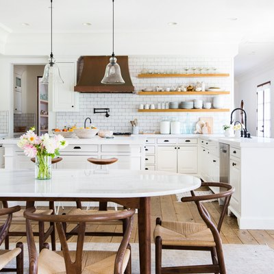 small kitchen idea with open concept layout and dining room with pendant lights and wishbone chairs