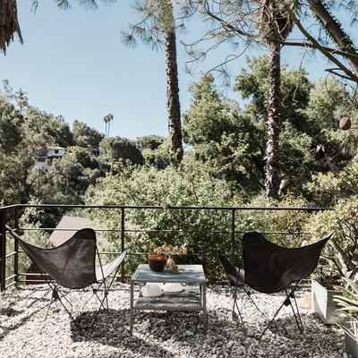 A second-story gravel patio with two black butterfly chairs, all surrounded by many trees