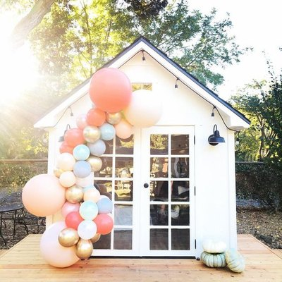 white she shed in backyard with colorful balloon display