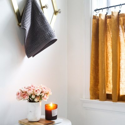 mustard-yellow bathroom curtain idea with cafe curtain in a bathroom window