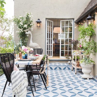 backyard patio with patterned tile and woven rattan chairs with open French doors