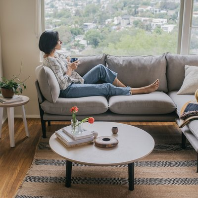 woman sitting on a couch with a coffee table nearby